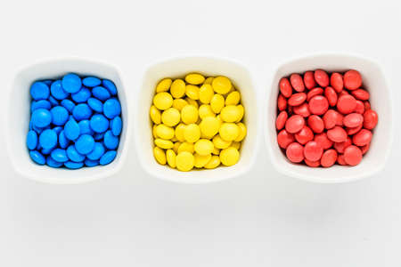 Three squared bowls with small red, yellow and blue coated chocolate candies similar to m&ms in a squared bowl isolated on white background, top view