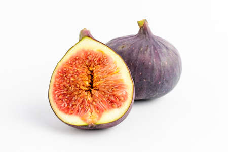 Fresh ripe organic figs on a white table, one whole fig and one sectioned in half, close up with soft focus, top view Standard-Bild