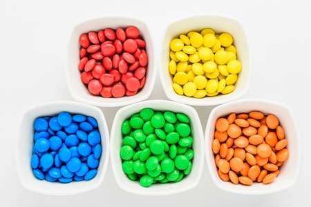 Five squared bowls with small red, yellow, blue, green and orange coated chocolate candies similar to m&ms in a squared bowl isolated on white background, top view