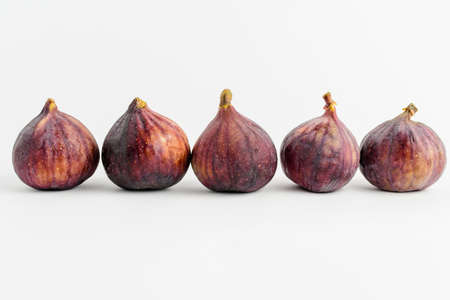 Five ripe organic figs diplayed in horizontal line on a white background, close up with soft focus