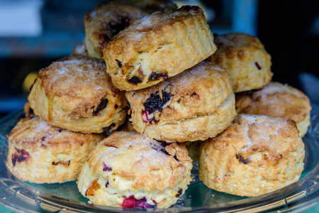 Freshly baked homemade English scones with dried fruits, displayed as a pyramid, available for sale at a café in London, side view of healthy food photographed with soft focus