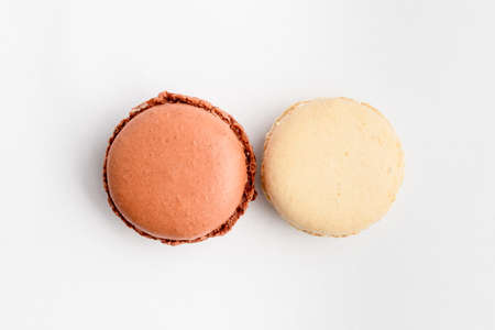 Top view of two sweet vivid brown chocolate and white vanilla French macaron isolated on white background, tasty French dessert on a table