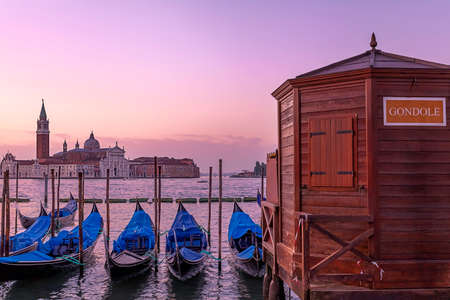 Sunset over San Giorgio Maggiore and deserted gondolas pier  photo