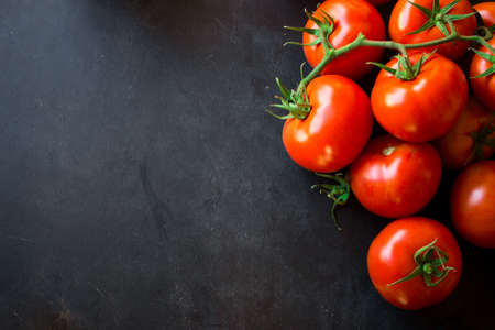 Mountain of red tomatoes on a wooden board