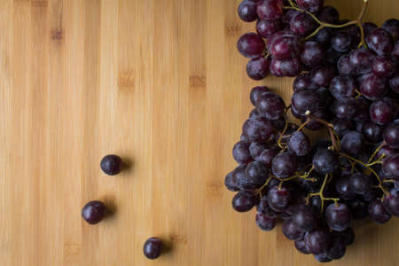Bunch of red grapes and grape grains on top of a wooden board Archivio Fotografico