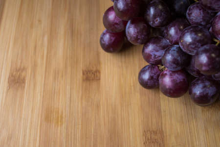 Bunch of red grapes on top of a wooden board