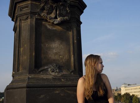 czech women: Prague, Czech Republic - October 13: The girl sit on the Charles Bridge next to the statue on October 13, 2015 in Prague, Czech Republic. Editorial