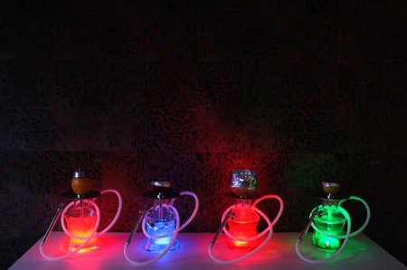 Several luminous hookahs in the dark on a table in the interior. Banque d'images