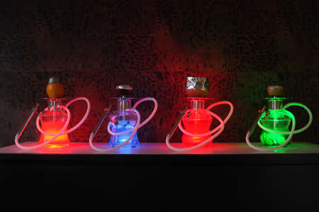 Several luminous hookahs in the dark on a table in the interior.