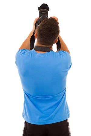 Joven fotógrafo con la cámara de la parte trasera, aislado en blanco Foto de archivo