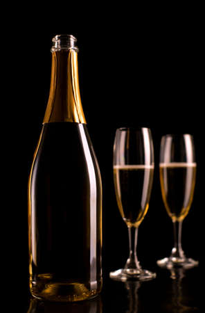 Champagne glasses and bottle on black background. New Year celebration.