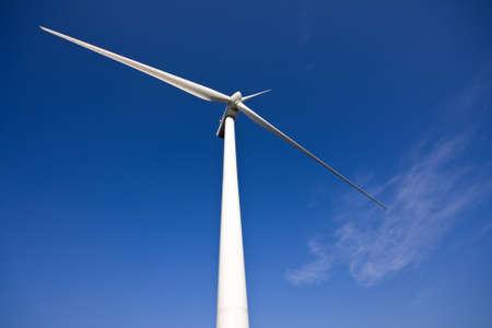 white wind turbine generating electricity on blue sky  免版税图像