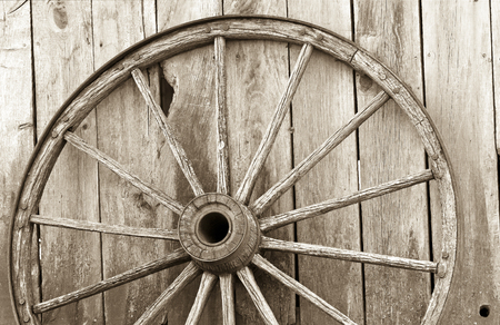 old wood farm wagon: Sepia image of an old, weathered wagon wheel, leaning up against a barn.