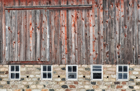 old window: Old, weathered red barn with field stone foundation