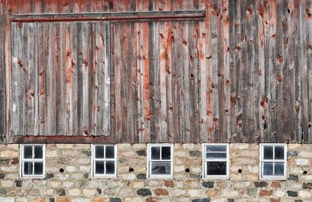 puertas viejas: Viejo, degradado granero rojo con base de piedra de campo Foto de archivo