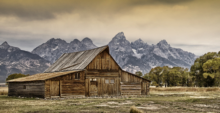 Old barn with the Grand Tetons in the background Stock Photo