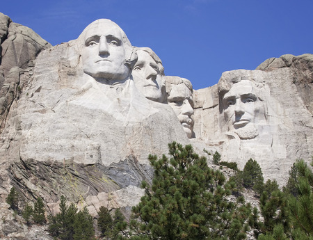 theodore roosevelt: Mount Rushmore National Monument in South Dakota, amongst a clear blue sky.