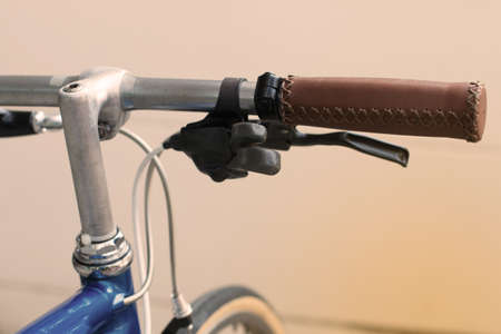 gripping bars: Detail on a vintage bicycle handle bar with leather cover, breke and shifter