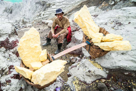 Worker at Ijen crater takes a break, East Java, Indonesia. Editorial