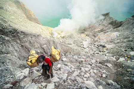 Worker at Kawah Ijen sulfer mine carries a basket of sulfur out of the crater