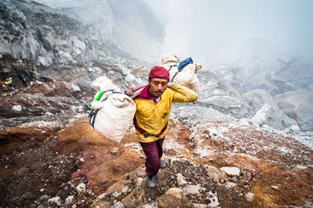 indo: Miner at Kawah Ijen in Java, Indonesia carries sulfer out of the crater