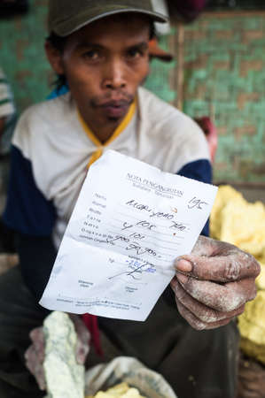 A worker at Kawah Ijen shows a receit with his earnings of the day