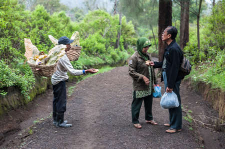 Worker at Ijen crater sells souvenirs to tourists Editorial