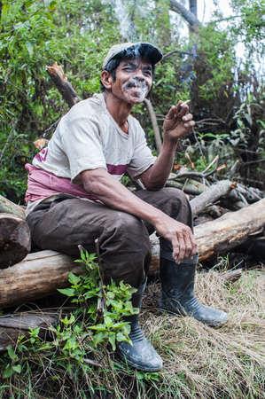Worker at Kawah Ijen takes a break and smokes
