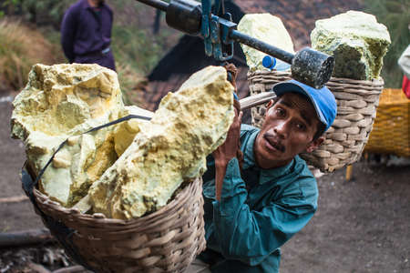 A worker at Kawah Ijen Java Indonesia weighs his basket of sulfur.