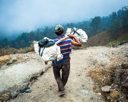 Arbeitskraft an der Ijen Schwefelmine in Java, Indonesien, trägt einen Korb von Schwefel Editorial