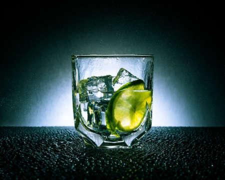 Gin-tonic met ijs en kalk op een donkere achtergrond met witte vlek Stockfoto