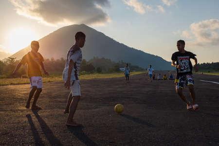 Jugendliche spielen Fußball auf dem Flugfeld von Bandaneira mit dem Vulkan im Hintergrund Lizenzfreie Bilder - 43484956
