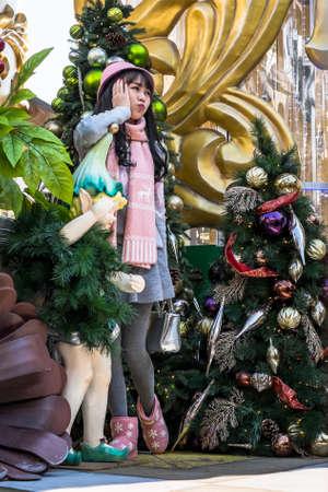 Mädchen in Hongkong posiert für ein Bild zwischen Weihnachtsschmuck Editorial