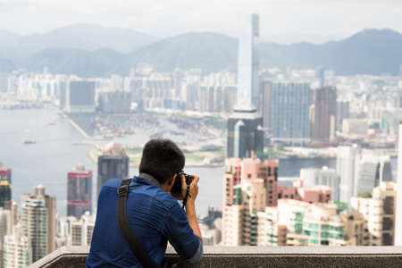 A tourist takes a photograph of the Hong Kong skyline from Victoria Peak.