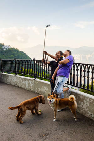 HONG KONG, CHINA - AUGUST 29, 2014: Tourists take a selfie selfie using a stick at Victoria Peak.