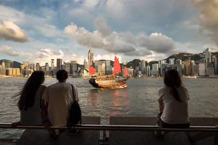HONG KONG, CHINA - JULY 14, 2014: Tourists watch a traditional Chinese junk sail suits at Victoria Harbour.