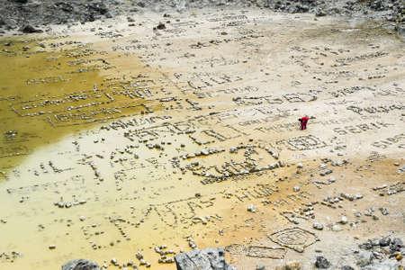 Ein Mann, der seine besondere Steine ??in den Krater des Vulkans Sibayak in Sumatra, Indonesien Verlegung. Lizenzfreie Bilder