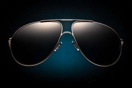 Trendy Sonnenbrille auf einem dunklen Hintergrund mit blauer Fleck Standard-Bild