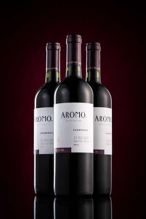 Drei Flaschen Aromo Carmenère Rotwein auf einem schwarzen Hintergrund mit lila Fleck. Aromo wurde 1922 gegründet. Editorial