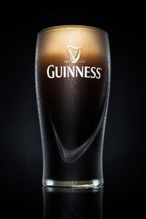 pint glass: Pint of Guinness, the popular Irish beer on a black background. Guinness is one of the most successful beer brands worldwide. Editorial