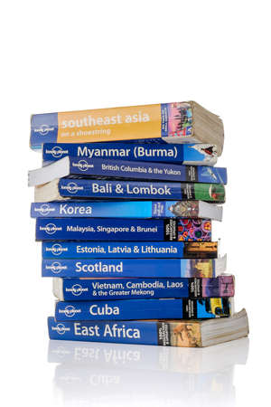 planets: EINDHOVEN, THE NETHERLANDS - JULY 25, 2015: A stack of Lonely Planet travel guidebooks isolated on a white background.