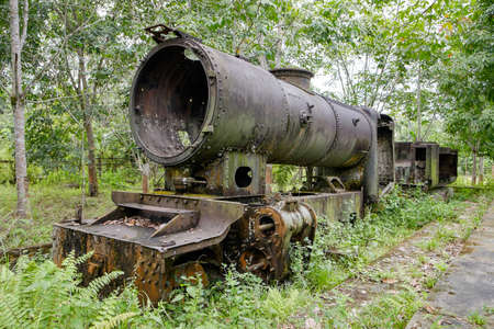 pekan: Old 2nd World War Japanese steam locomotive rusting away in a rubber plantation near Pekanbaru, Sumatra, Indonesia. Editorial