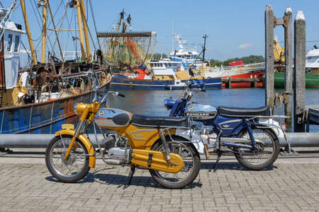 mopeds: STELLENDAM, THE NETHERLANDS - June 27, 2015: Two vintage Zndapp mopeds parked in a harbour. Zndapp was a major German motorcycle manufacturer founded in 1917 in Nuremberg Editorial
