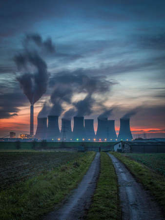 Power station cooling towers in front of a dramatic orange sunset sky Stock fotó