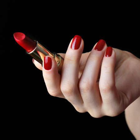 Red lipstick in elegant female hand isolated on black background Stock Photo