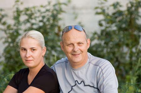 Senior man sitting next to yong wife