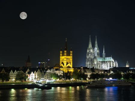 Night Cologne Cathedral from Rhine river with moon.