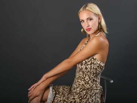 Blonde young woman sits with arms on ones knee and looks. Stock Photo