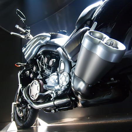 Motorbike with big exhaust pipe against a dark background.