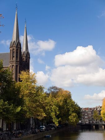 Cathedrals and canal against blue skies in Amsterdam, Netherlands.